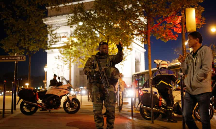 An armed soldier secures a side road near the Champs Elysees after the incident