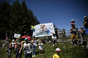 """Supporters cheer along the road with placards reading """"Long life the Tour de France""""."""