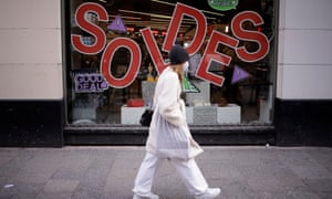 A woman walks past sale signs on shop windows in Paris, France, 20 January 2021.