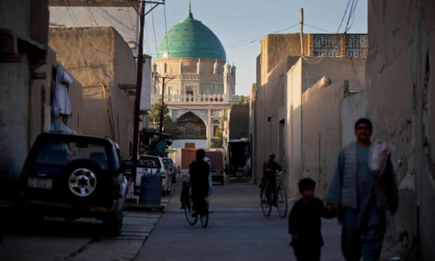 A father and son walk in the centre of Kandahar