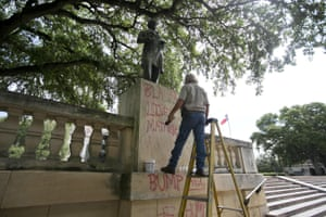 An employee removes graffiti from a statue of Jefferson Davis at the University of Texas in Austin