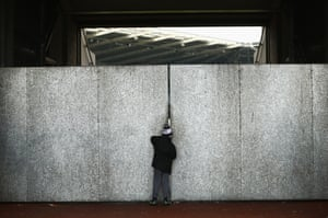 A young Swansea fan watches through a gap in the wall as the Swans lose 3-0 to Bournemouth at the Liberty Stadium.