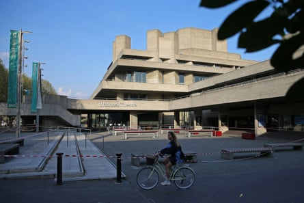 A cyclist rides past the National Theatre with its forecourt taped off to prevent use.