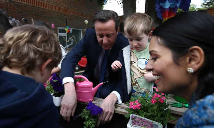 David Cameron plants flowers with children during a visit to a nursery in London