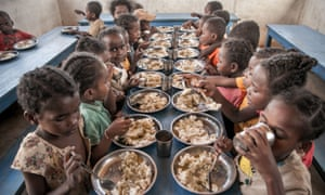 Schoolchildren eat lunch offered by the World Food Programme during a drought in Madagascar last year