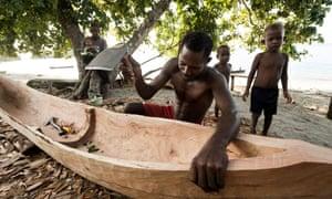 A man carves a canoe