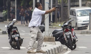 A plainclothes police officer aims his gun at attackers during a gun battle following explosions in Jakarta, Indonesia
