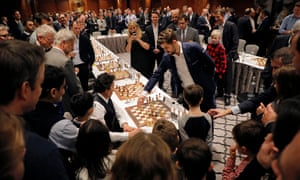 Magnus Carlsen with one of his 21 opponents at the Four Seasons Hotel in London.