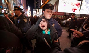 A woman reacts as New York City police officers push people out of an intersection in Times Square during protests.