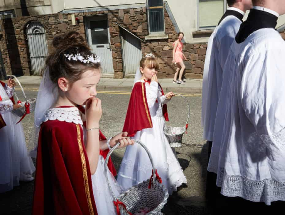 Eight-year-old girls dressed as Brides of Christ kiss petals representing the blood of Jesus, at a Eucharistic procession in Cork city