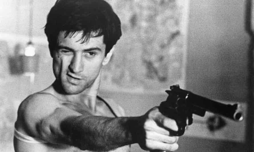 Robert De Niro closing one eye as he points a gun in Taxi Driver