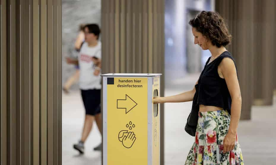 A woman uses a disinfection column at the Breda train station in the Netherlands