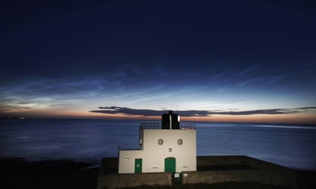 Noctilucent clouds forming over Bamburgh lighthouse in Northumberland, UK, in June.