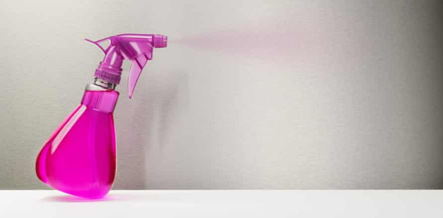 A bright pink spray bottle spritzing out some cleaning fluid