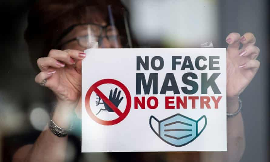 """A woman puts a sign saying """"no face mask no entry"""" in a shop window in Newport, Wales, 14 September 2020."""