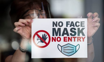 "A woman puts a sign saying ""no face mask no entry"" in a shop window in Newport, Wales, 14 September 2020."
