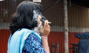 A Bangladeshi woman smokes a cigarette in Dhaka