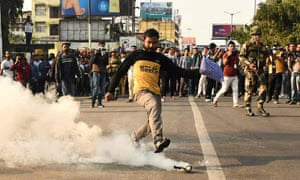 A demonstrator kicks a teargas shell fired by police to disperse protesters.