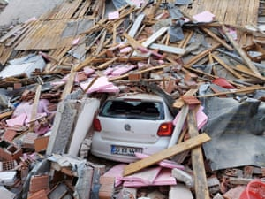 A collapsed building and crushed car in İzmir