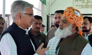 Pakistan's defence minister (left) and the chief of the country's religious hardline party Jamiat Ulema-e-Islam talk at Parliament House in Islamabad.