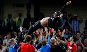 Huddersfield Town players throw manager David Wagner in the air as they celebrate staying in the Premier League.