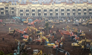 Workers driving excavators at the construction site of a new field hospital being built in Wuhan, Hubei Province, China.