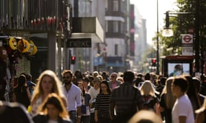 Pedestrians throng the busy Oxford street in central London yesterday.