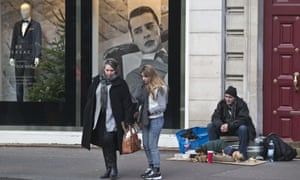 People walk past a homeless man sitting on his luggage next to a luxury shop in Paris.
