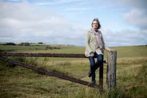Sally Boys sits on a gate in front of the South Downs National Park.
