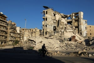 A man rides a bicycle past damaged buildings in the rebel-held Tariq al-Bab neighborhood