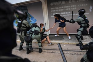 Hong Kong police chase down a couple wearing facemasks in the Central district in Hong Kong on October 5, 2019.