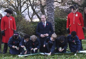 Lonon, UK Prince William, Duke of Cambridge, centre, watches children planting seeds during a visit to the Living Memory and Centenary Fields Projects yesterday