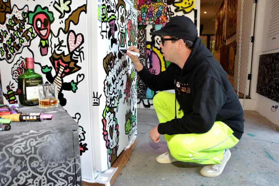 Miami artist Vic García painting a new community refrigerator.
