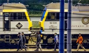 Migrants walk along railway tracks at the Eurotunnel terminal.
