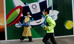 A man jogs past a wall depicting the mascot for Tokyo's 2020 Olympics