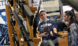 An attendee inspects a rifle during the NRA Annual meeting in Dallas, Texas.