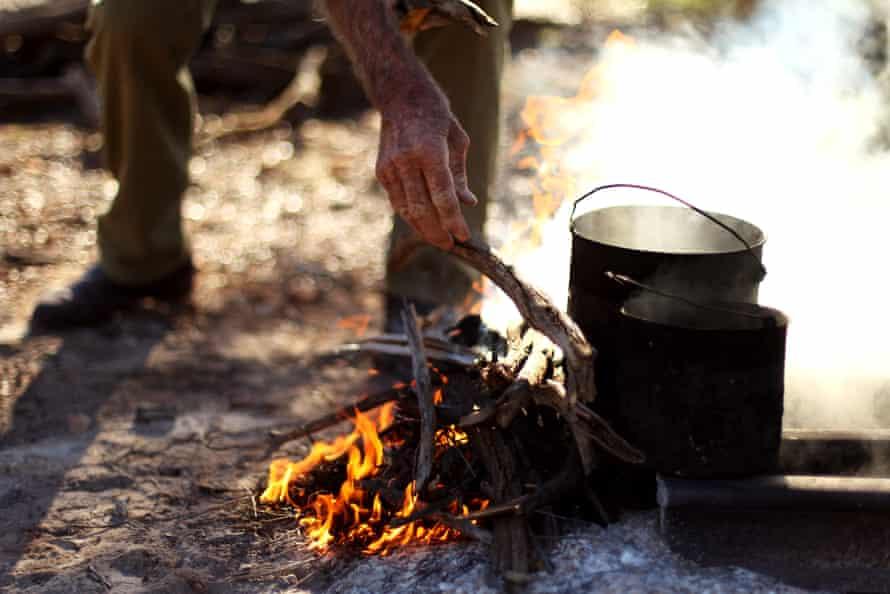 a man puts a stick on a fire boiling a billy