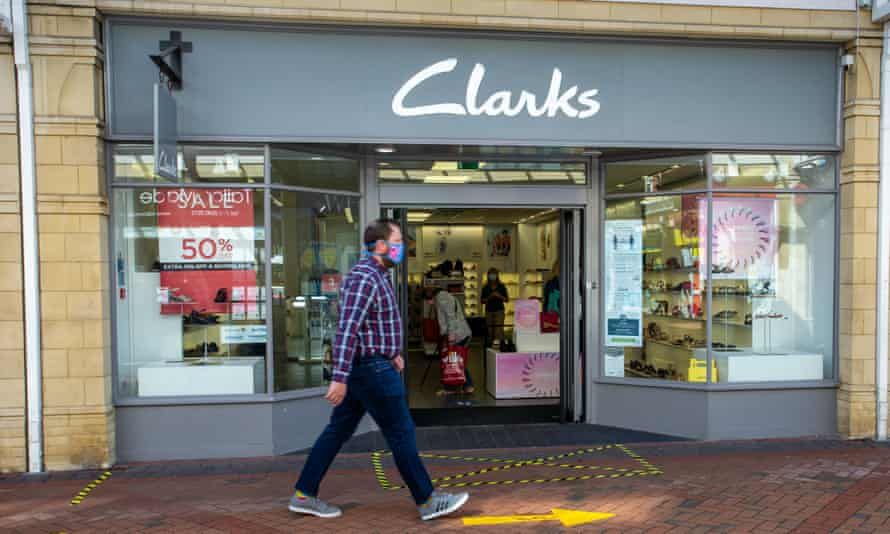 A shopper walks past Clarks shoe store in Castle Court shopping centre in Caerphilly, Wales