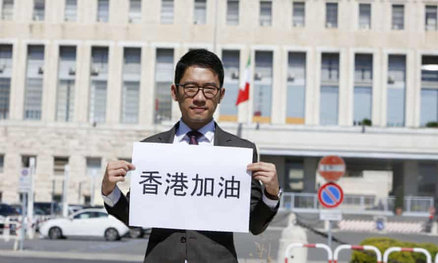 """Exiled Hong Kong's activist Nathan Law holds a sign reading in Chinese """"Go Hong Kong"""" as he meets the press outside of the Italian Foreign Ministry."""