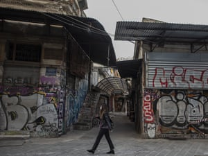 A woman wearing a face mask walks outside shuttered shops in Monastiraki district, central Athens. Greek authorities have registered a new record high of 41 Covid-19 deaths, three days into a new lockdown, but a drop in new infections.