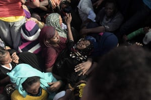 A woman faints while refugees and migrants wait to be rescued by members of Proactiva Open Arms NGO