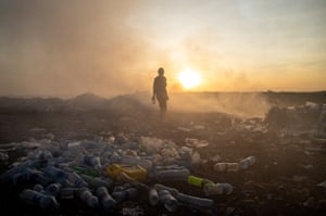 A waste picker collects plastic bottles on a burning dump in Dar es Salaam, Tanzania.