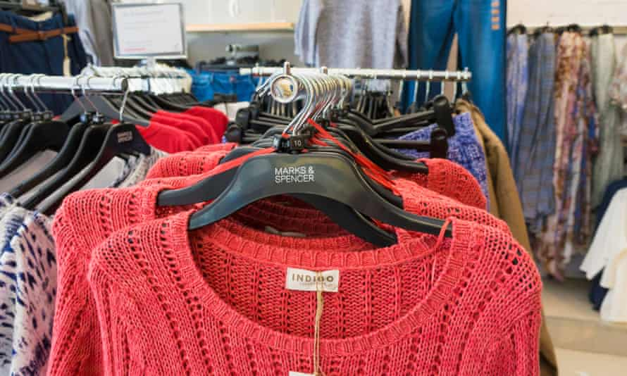 red jumpers and other clothes on the rails at M&S