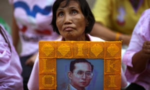 A well-wisher holds a picture of Thailand's King Bhumibol Adulyadej