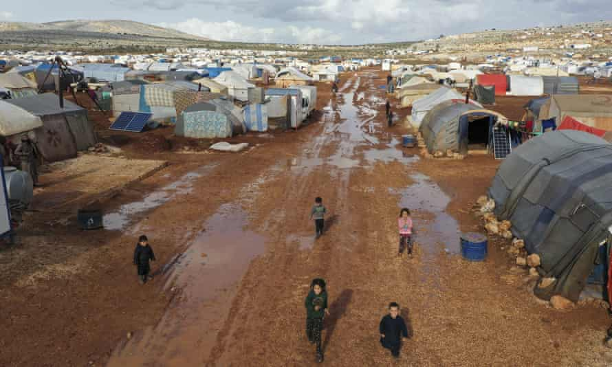 Syrian refugees walk through a camp for displaced people near the village of Kafr Aruq, in Idlib province, Syria.