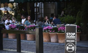 People eating outside at a restaurant, in London,in late July.