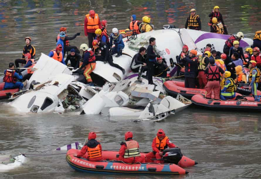 Rescue personnel search for passengers from the wreckage of a TransAsia ATR 72-600 turboprop plane that crash-landed into the Keelung river outside Taiwan's capital Taipei.