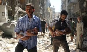 Men carry babies through the rebel-held Salihin neighbourhood of Aleppo on Sunday.