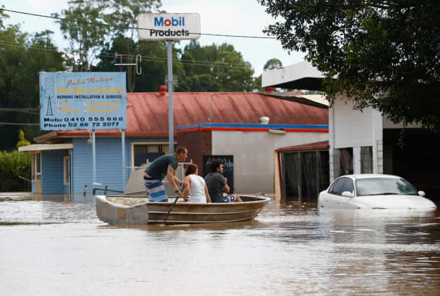 Queensland residents use a boat to cross a flooded street.