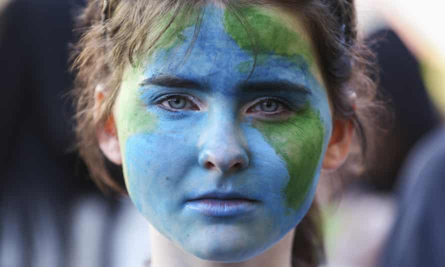 A protester with the Earth painted on their face